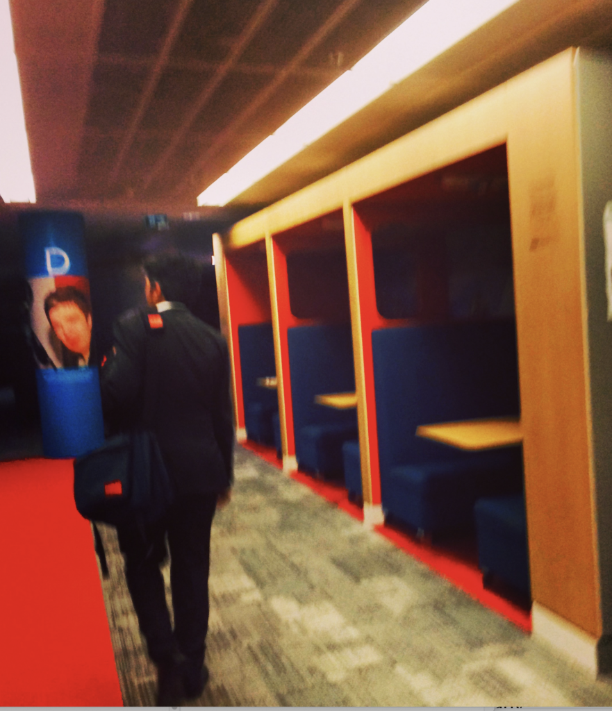 The image shows a windowless hallway lit by fluorescent light. The camera is somewhat askew, creating different angles. Dark, plush booths, apparently for dining, are on the right wall. The room has points of red and navy blue. A man in a suit stands with his back to the camera, looking slightly to the left. A navy blue column has a blurry photograph of a face